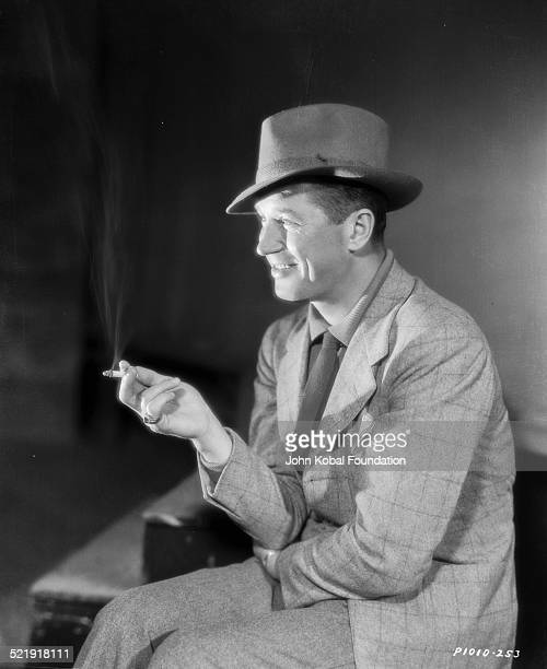 Portrait of actor Maurice Chevalier wearing a hat and smoking a cigarette for Paramount Pictures 1932
