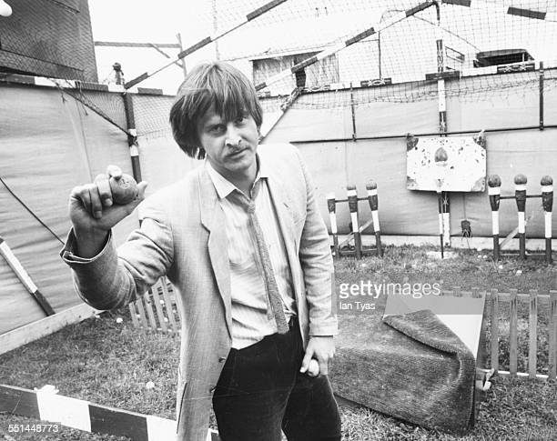 Portrait of actor Trevor Eve preparing to knock over a coconut at a shy filming an episode of the BBC show 'Shoestring' at Glastonbury England circa...