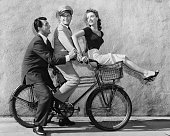 Portrait of actors Dean Martin Dewey Martin and Anna Maria Alberghetti ringing a bicycle together through the studio backlot where they are filming...