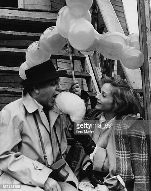 Portrait of actors Naunton Wayne and Joyce Redman sitting on the steps on a helter skelter eating candy floss together at Pinner Fair London May 19th...