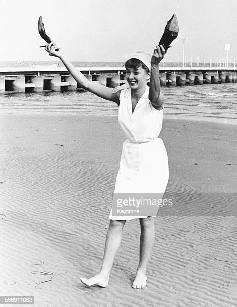 Portrait of actress Anastasiya Vertinskaya laughing as she walks barefoot on the beach holding her high heel shoes attending the film festival in...