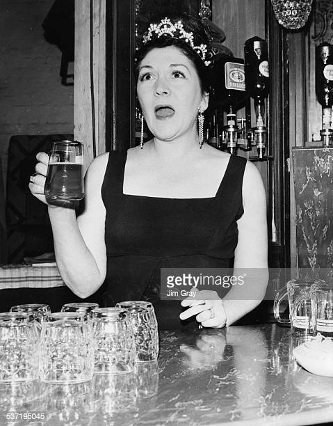 Portrait of actress and singer Queenie Watts singing as she drinks a pint of lager and smokes a cigarette during rehearsals for the show 'Old Time...