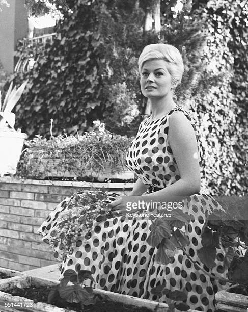 Portrait of actress Anita Ekberg sitting outdoors wearing a polka dot dress at her home in Rome circa 1960