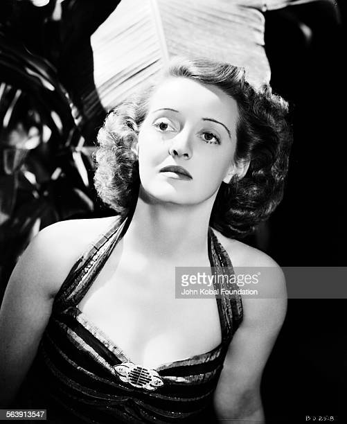 Portrait of actress Bette Davis wearing a striped halterneck dress for Warner Bros Studios 1939