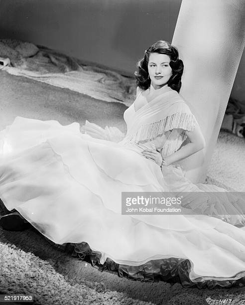 Portrait of actress Cyd Charisse sitting with the skirt of her dress laid out around her for MGM Studios April 4th 1946