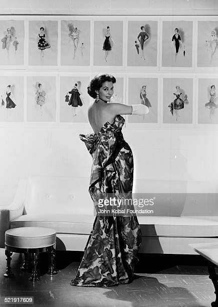 Portrait of actress Cyd Charisse turning with her back toward the camera and wearing an evening gown for MGM Studios 1950