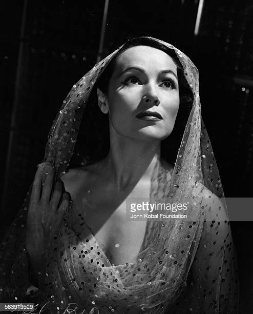 Portrait of actress Dolores del Rio wearing a sequin headscarf 1946