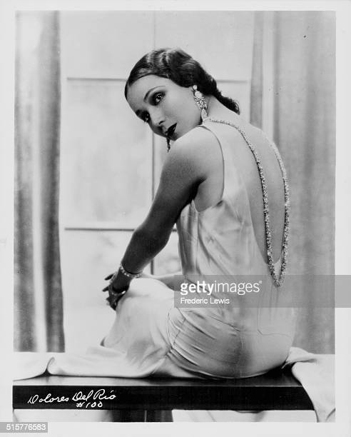 Portrait of actress Dolores del Rio wearing a silk evening dress with her back to camera circa 1930
