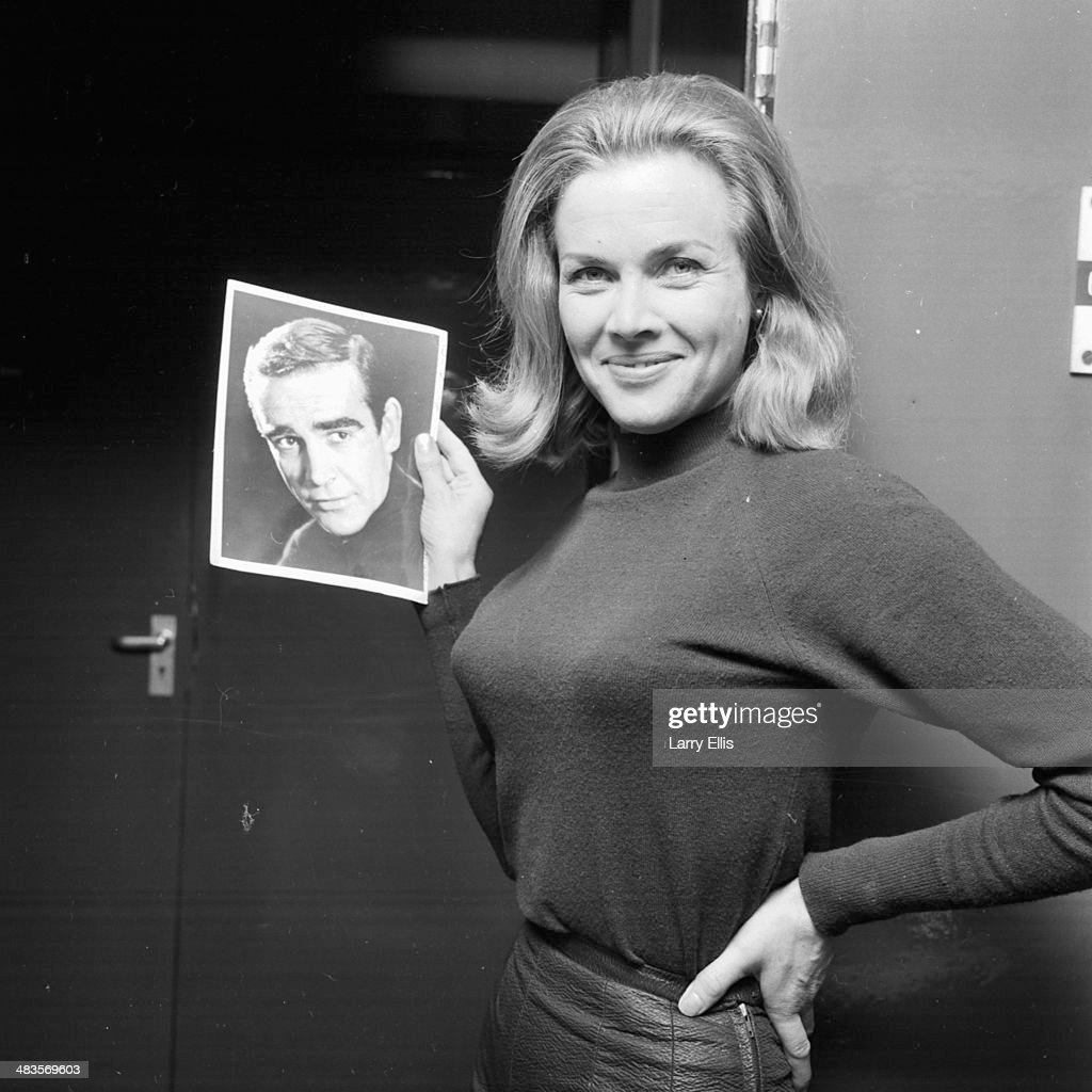 Portrait of actress Honor Blackman holding a picture of actor Sean Connery, following her being cast in the new James Bond film, 8th January 1964.