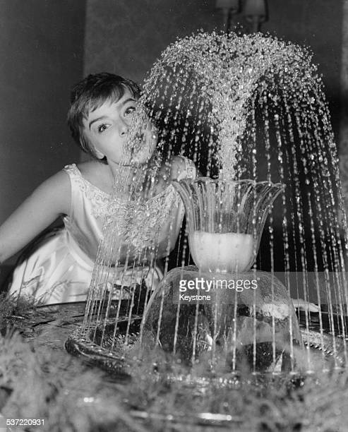 Portrait of actress Janet Munro drinking from a water fountain in the auditorium of the Astoria at the premiere of the film 'Sleeping Beauty' London...