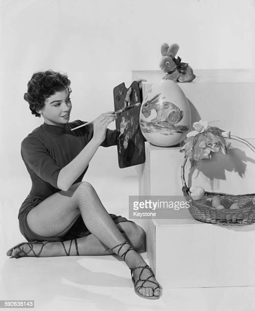 Portrait of actress Leslie Caron painting an Easter egg for her first Easter in America circa 1955