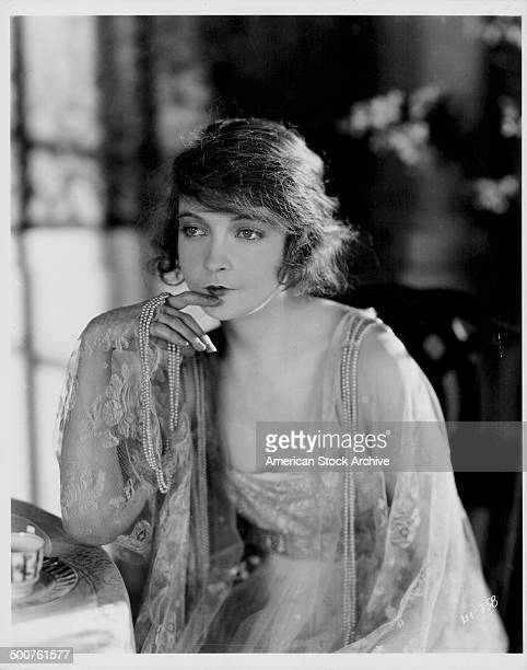 Portrait of actress Lillian Gish holding a string of pearls whilst sitting at a dressing table circa 19201930