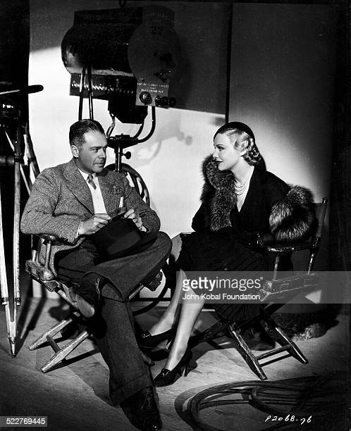 Portrait of actress Madeleine Carroll resting between takes on a film set with another actor with Paramount Pictures 1935