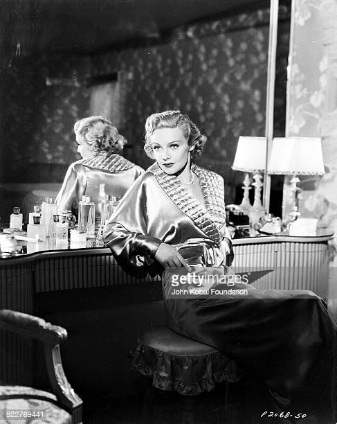 Portrait of actress Madeleine Carroll sitting at a dressing table and wearing a silk robe with Paramount Pictures 1936