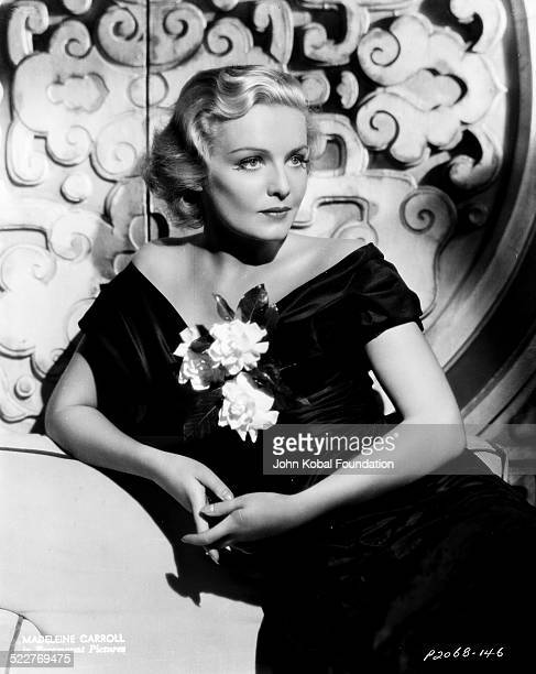 Portrait of actress Madeleine Carroll wearing a black off the shoulder dress and holding a flower with Paramount Pictures 1935