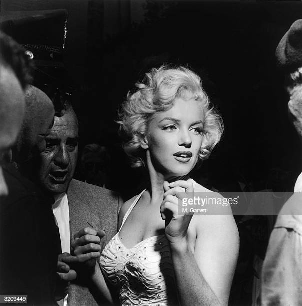 A portrait of actress Marilyn Monroe surrounded by reporters and fans outside Grauman's Chinese Theater in Hollywood California