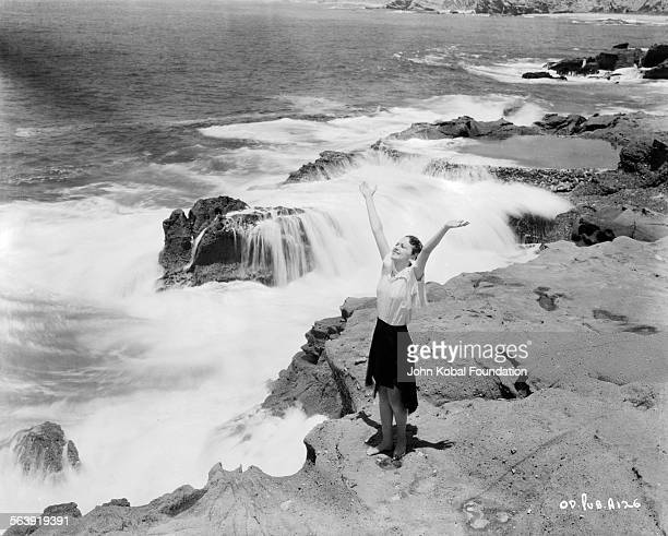 Portrait of actress Olivia de Havilland raising her arms in the air as she stands on a rock face overlooking the sea as she appears in the film...