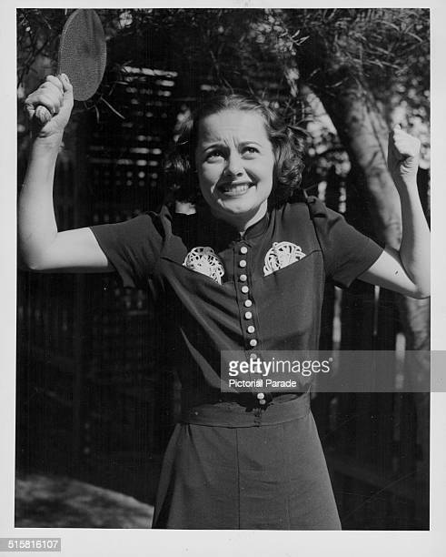 Portrait of actress Olivia de Havilland shrugging her shoulders and holding a ping pong paddle circa 1940