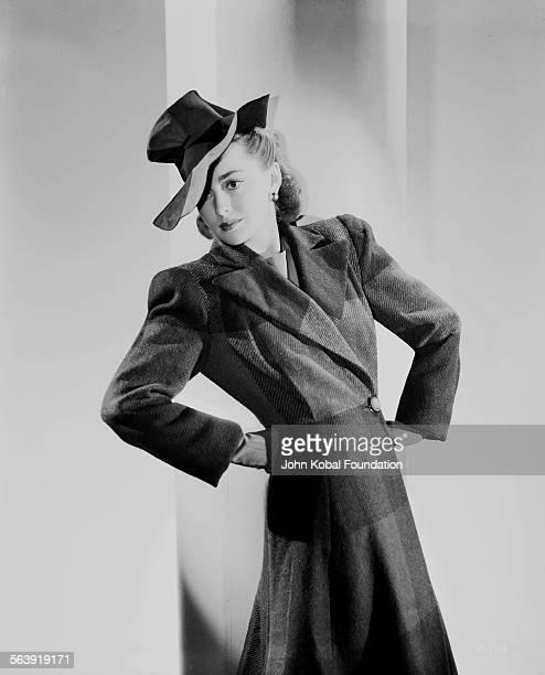 Portrait of actress Olivia de Havilland wearing a hat and overcoat for Warner Bros Studios 1938