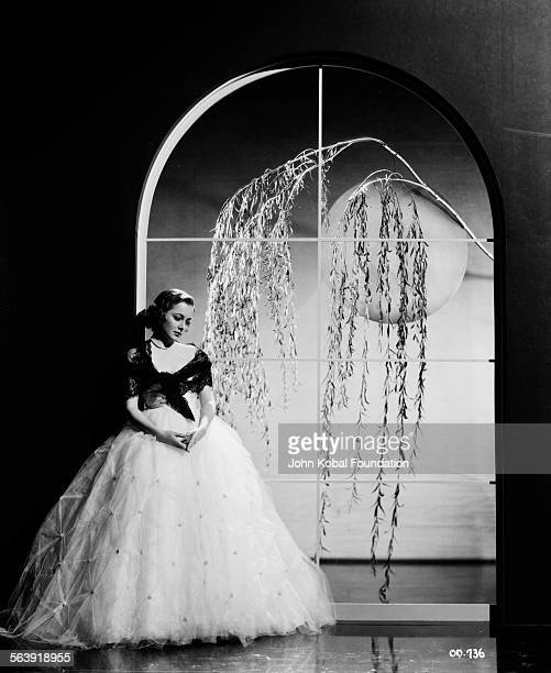Portrait of actress Olivia de Havilland wearing a large ball gown next to a window as she appears in the film 'Captain Blood' for Warner Bros Studios...