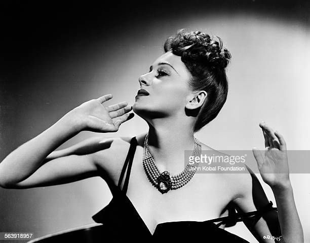 Portrait of actress Olivia de Havilland wearing her hair up and a pearl necklace for Warner Bros Studios 1937