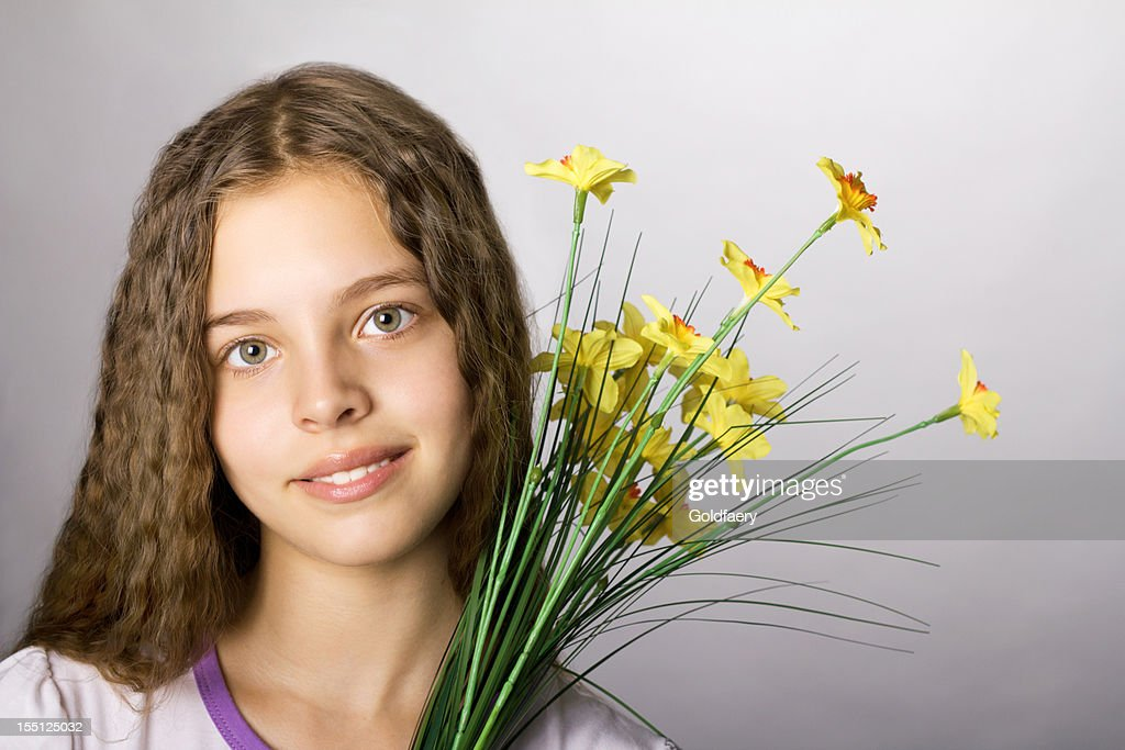Portrait of adorable cheerful girl with flowers.