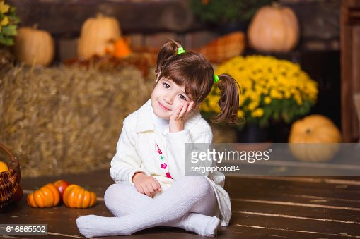 Portrait of adorable smiling girl posing with orange pumpkin in : Stock Photo