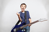 Portrait of adorable young boy playing electric guitar. kid shows the rock and roll gesture