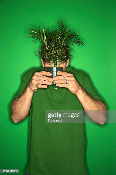 Portrait of adult Caucasian man on green background holding plant in front of his face.