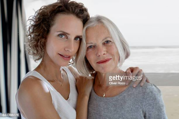 Portrait of adult daughter embracing mother