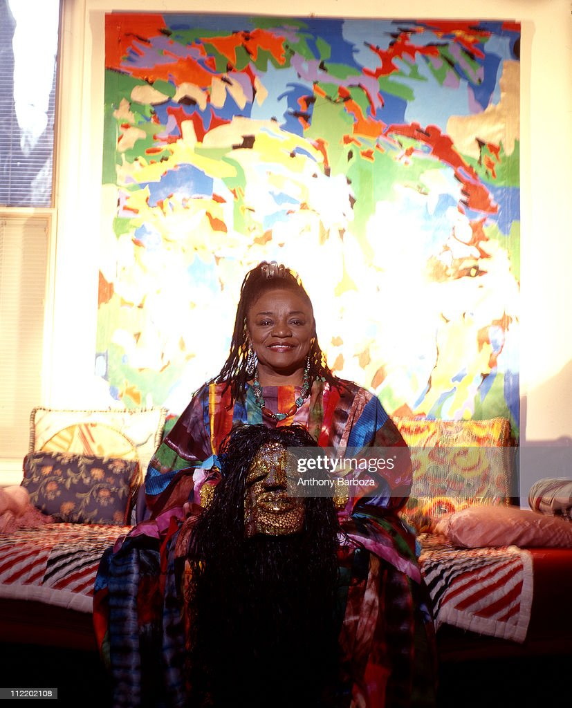 Portrait of African American artist Faith Ringgold, seated and holding one of her pieces, New Jersey, 1999.