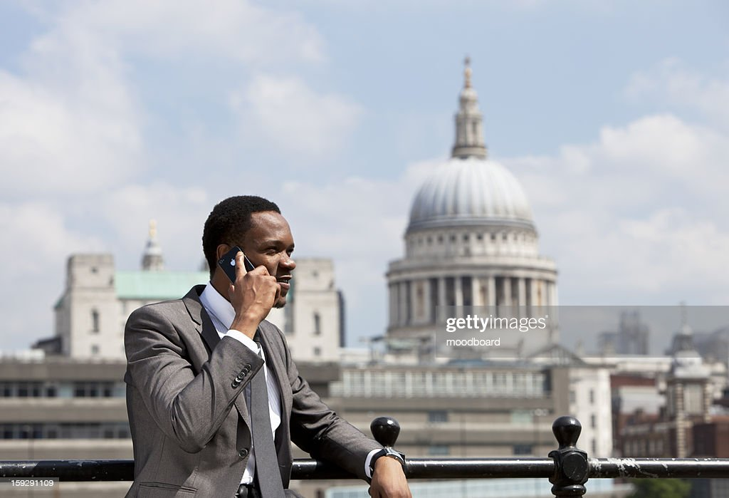 Portrait of African American businessman talking on Cell phone in London : Stock Photo
