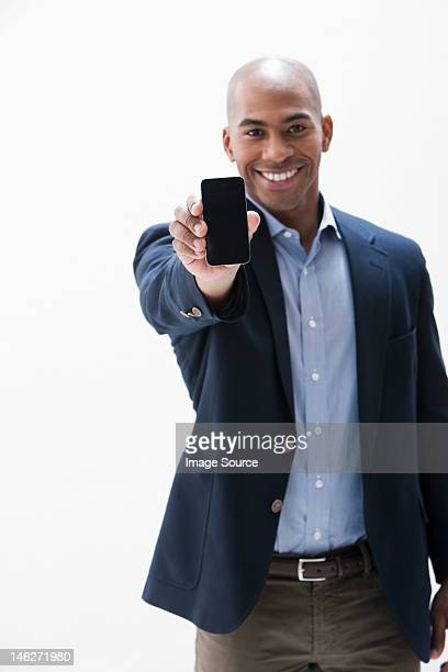Portrait of African American man holding cellphone, studio shot