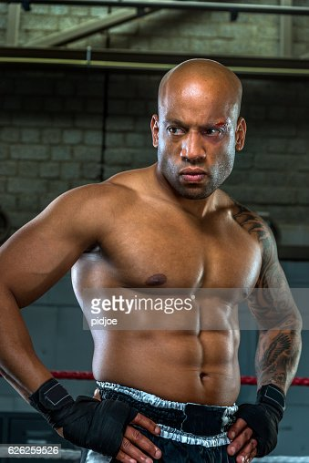 Portrait of aggressive and wounded boxer  in boxing gym