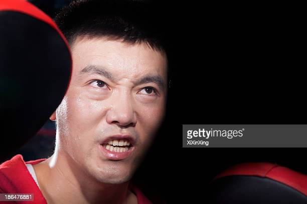 Portrait of aggressive looking boxing coach at the gym holding pads