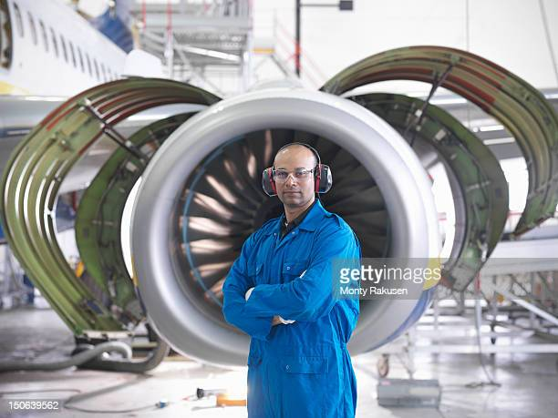 Portrait of aircraft engineer in front of 737 engine in hangar