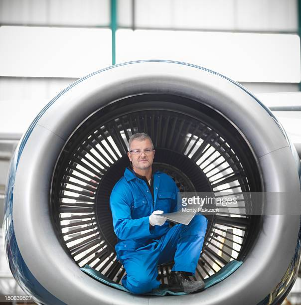 Portrait of aircraft engineer working on jet 737 engine in airport