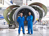 Portrait of aircraft engineers in front of 737 engine in hangar