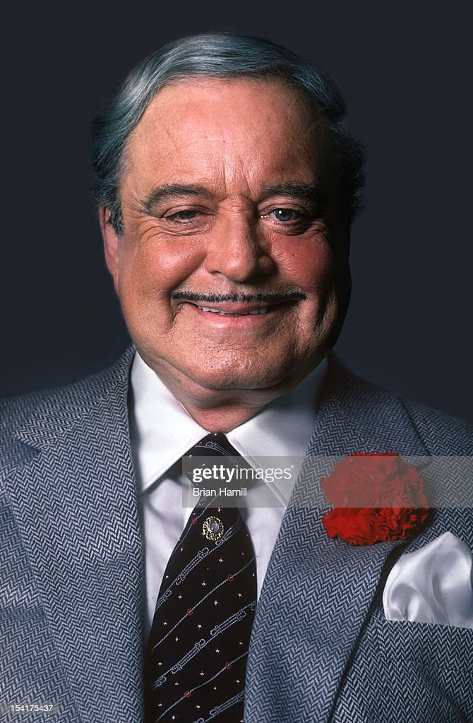 Portrait of American actor and comedian <a gi-track='captionPersonalityLinkClicked' href=/galleries/search?phrase=Jackie+Gleason&family=editorial&specificpeople=203285 ng-click='$event.stopPropagation()'>Jackie Gleason</a> (1916 - 1987), in a grey suit with a red carnation in jacket lapel, as he smiles, New York, New York, July 1985.