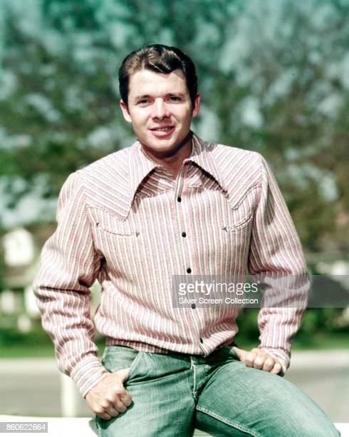 Portrait of American actor and decorated World War 2 veteran Audie Murphy as he poses thumbs in the pockets of his jeans mid 1950s