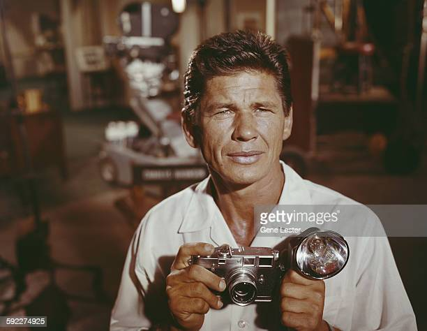 Portrait of American actor Charles Bronson as he poses on set with a camera in his hands circa 1958