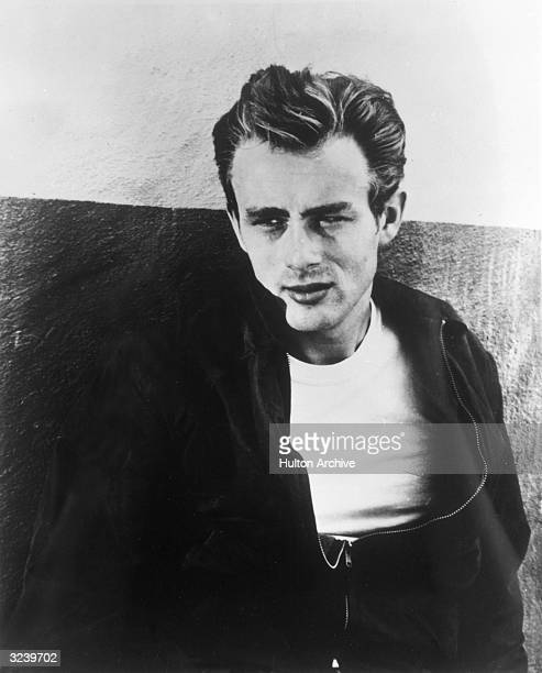 Portrait of American actor James Dean leaning against a wall on the set of director Nicholas Ray's film 'Rebel Without a Cause'