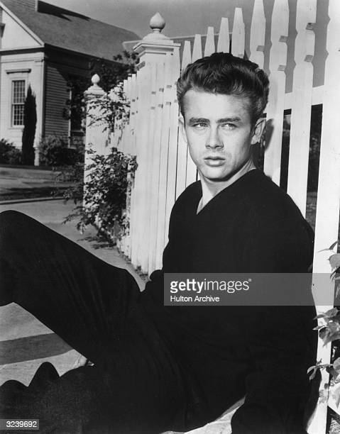Portrait of American actor James Dean sitting on the sidewalk leaning against a white picket fence on the set of director Nicholas Ray's film 'Rebel...