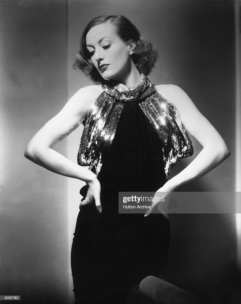 Portrait of American actor Joan Crawford standing with her hands on her hips in a dress with a sequined neckline designed by Adrian for her role in...