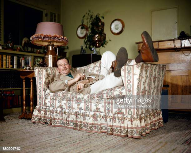 Portrait of American actor John Wayne a cigarette in one hand as he relaxes feet up on the arm of a couch 1950s