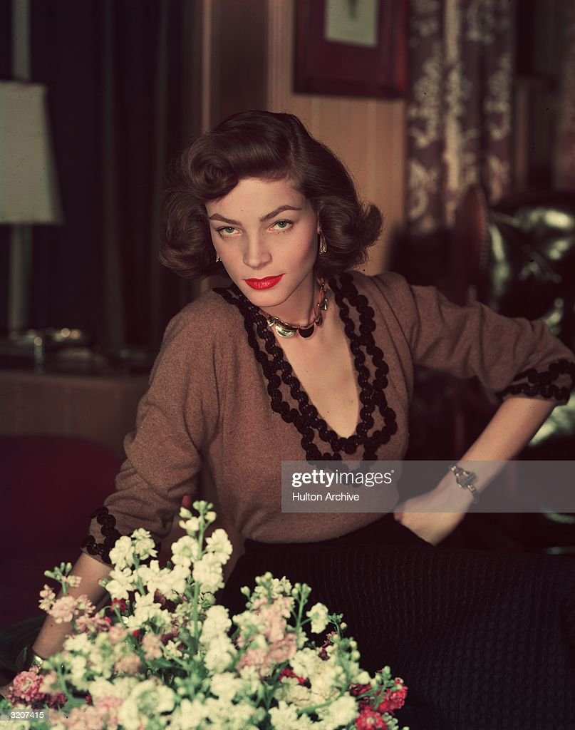 Portrait of American actor Lauren Bacall standing and leaning one hand on a table beside a vase of flowers with her other hand on her hip She wears a...