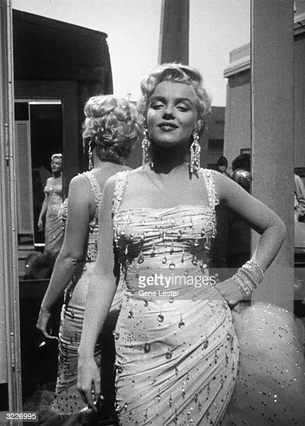 Portrait of American actor Marilyn Monroe posing in a white beaded gown on the 20th Century Fox studios set of director Walter Lang's film 'There's...