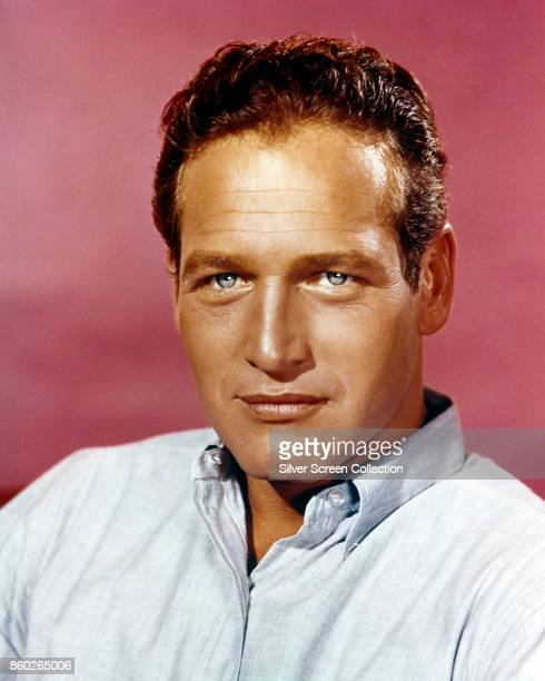 Portrait of American actor Paul Newman as he poses against a pale red background 1960s
