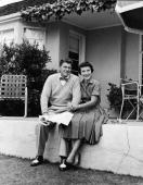 Portrait of American actor Ronald Reagan and his wife Nancy Reagan sitting outdoors on a patio wall circa 1955