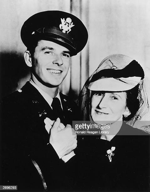 Portrait of American actor Ronald Reagan smiling and holding his mother Nelle's hand He wears his US Army uniform and cap